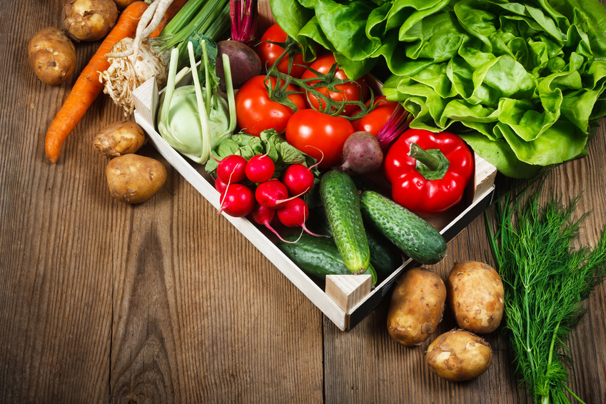 Fresh vegetables in wooden box on rustic background